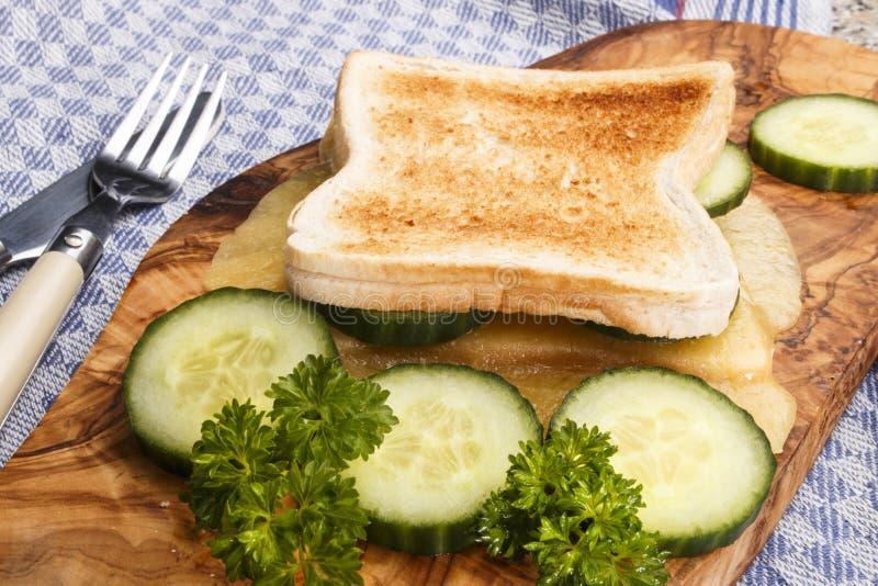Geroosterd brood met gesmolten Ierse milde cheddar en komkommerplakken royalty-vrije stock fotografie