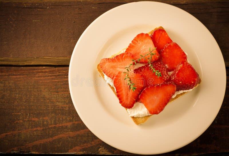 Geroosterd brood met roomkaas, aardbeien en thyme op houten lijst stock foto