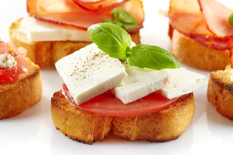Geroosterd brood met verse geitkaas en tomaat stock foto