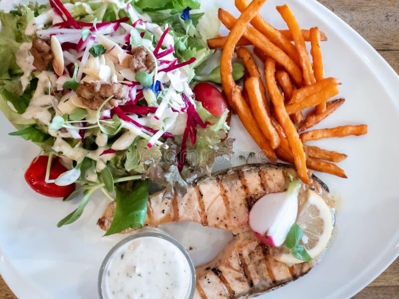 Geroosterd die vissenlapje vlees met salade, Frieten en een saus wordt gediend royalty-vrije stock foto