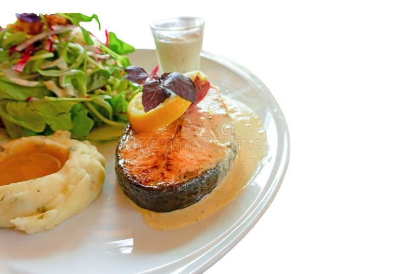 Geroosterd die zalmlapje vlees op witte plaat met gemengde plantaardige salade wordt gesneden, fijngestampt aardappels en bovenst stock foto's