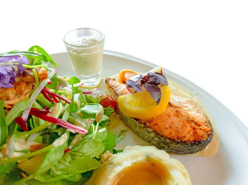 Geroosterd die zalmlapje vlees op witte plaat met gemengde plantaardige salade wordt gesneden, fijngestampt aardappels en bovenst royalty-vrije stock afbeeldingen