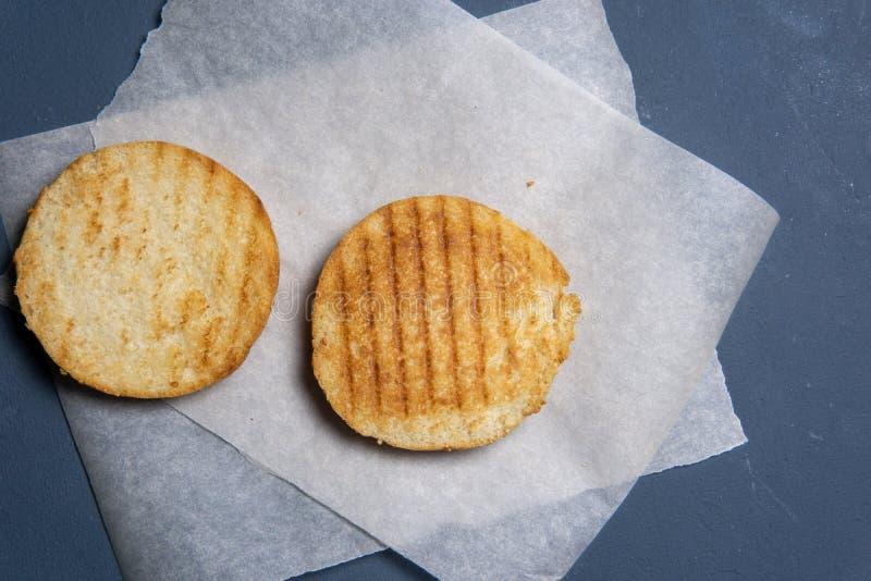 geroosterd en besnoeiing in half hamburgerbroodje op papier royalty-vrije stock fotografie