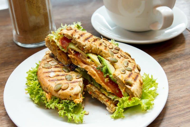 Geroosterd gevuld ongezuurd broodje met salade op een witte plaat royalty-vrije stock afbeelding