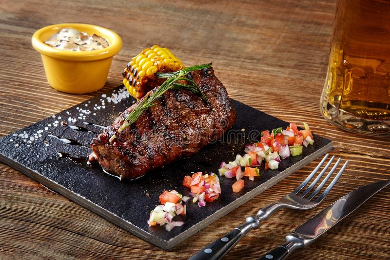 Geroosterd haasbiefstuklapje vlees roastbeef en paddestoelensaus op zwart scherp raad en glas bier op houten achtergrond royalty-vrije stock fotografie