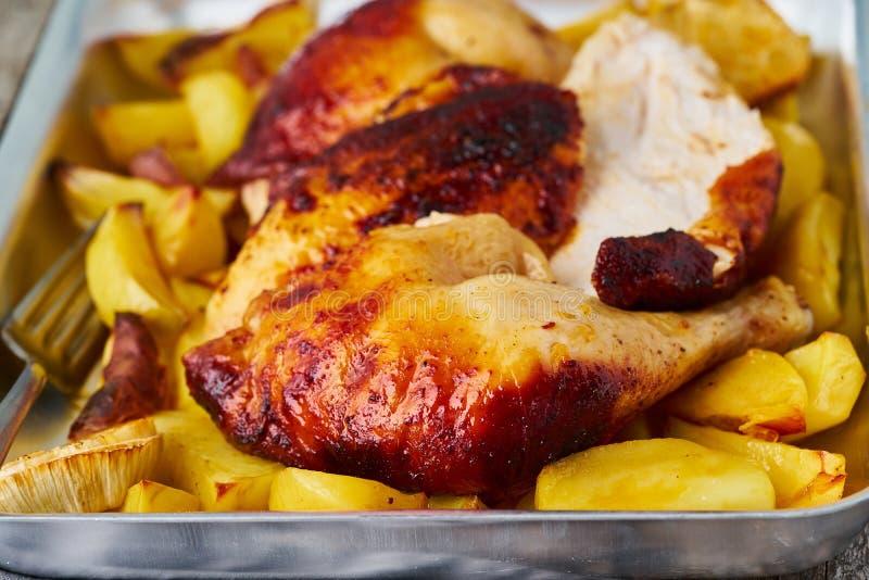 Geroosterd kippenvlees, been, dij met aardappelen in de schil Het zijaanzicht, sluit omhoog stock afbeeldingen