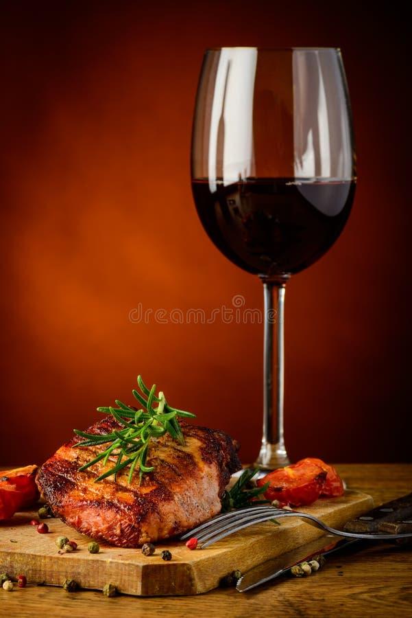 Geroosterd lapje vlees en glas rode wijn stock foto's