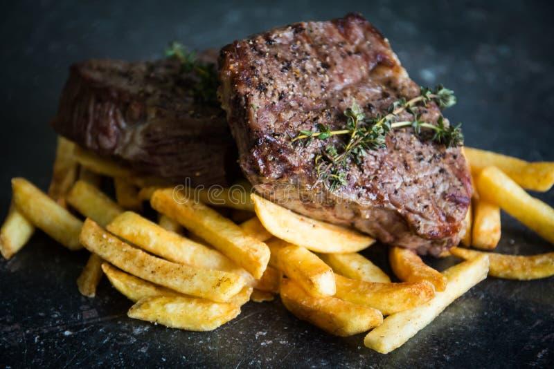 Geroosterd lapje vlees met frieten stock foto