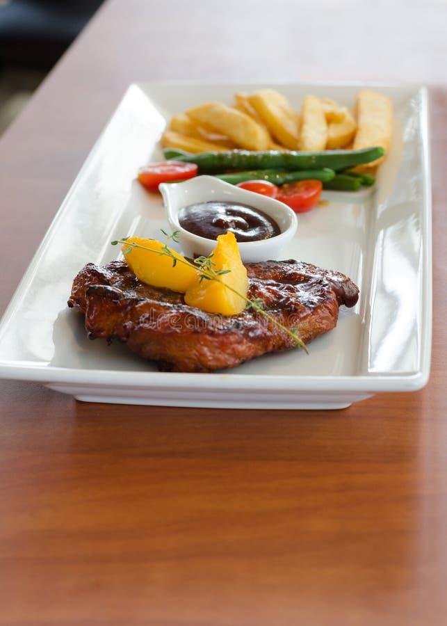 Geroosterd lapje vlees met frieten stock afbeeldingen