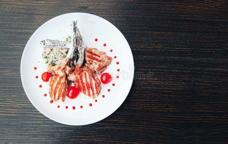 Geroosterd lapje vlees op een been met tomaten op een witte plaat Hete vleesschotels Hoogste mening royalty-vrije stock afbeeldingen