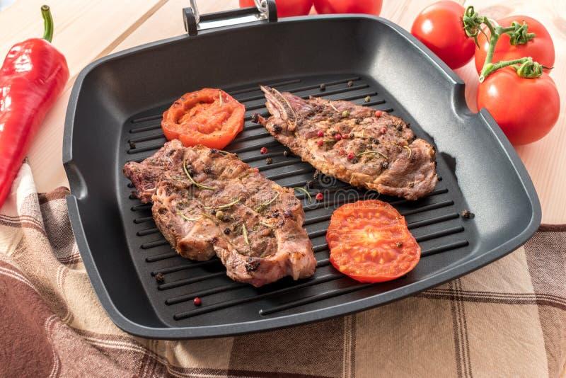 Geroosterd lapje vlees op grillpan met tomaten royalty-vrije stock afbeeldingen