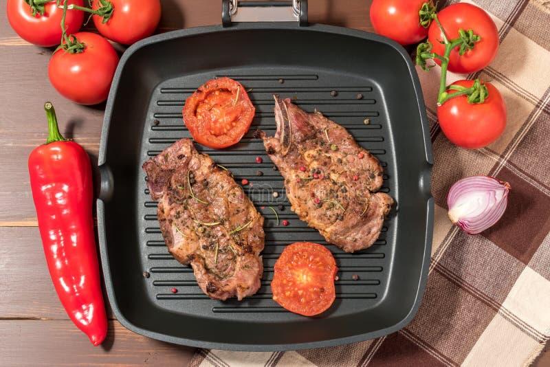 Geroosterd lapje vlees op grillpan met tomaten stock foto