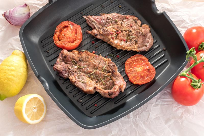 Geroosterd lapje vlees op grillpan met tomaten en citroen stock foto's