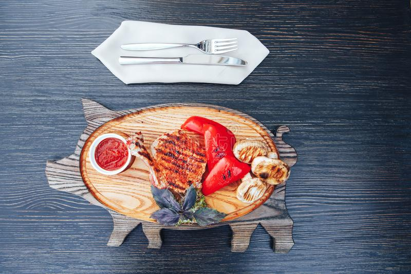 Geroosterd Ribeye-Lapje vlees op been en groenten en bbq saus bij het snijden van houten raad Hete vleesschotels stock fotografie