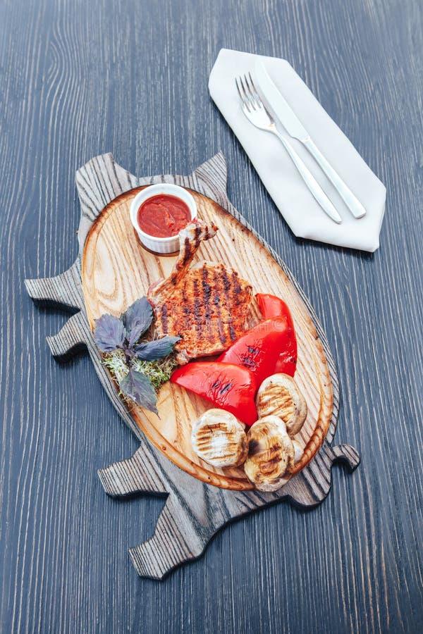 Geroosterd Ribeye-Lapje vlees op been en groenten en bbq saus bij het snijden van houten raad Hete vleesschotels stock foto's