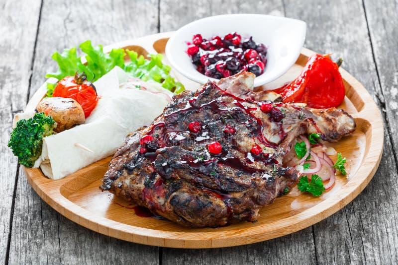 Geroosterd Ribeye-Lapje vlees op been met bessensaus, verse salade en geroosterde groenten op scherpe raad op houten achtergrond stock foto
