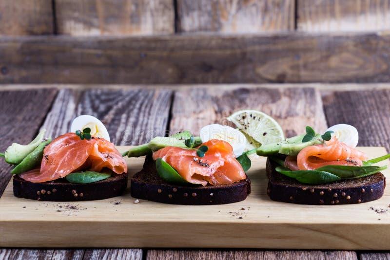 Geroosterd roggebrood met gerookte zalm en verse groene groenten royalty-vrije stock foto