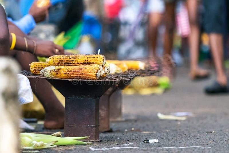Geroosterd - rooster graan op een steenkoolfornuis in de straat in Bemoeiziek is, Madagascar royalty-vrije stock foto's