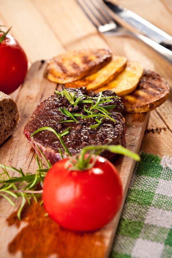 Geroosterd rundvleeslapje vlees, aardappelen in de schil en groente op houten brood royalty-vrije stock foto's