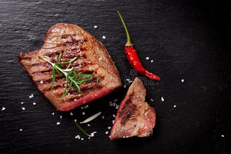 Geroosterd rundvleeslapje vlees met rozemarijn, zout en peper stock afbeelding