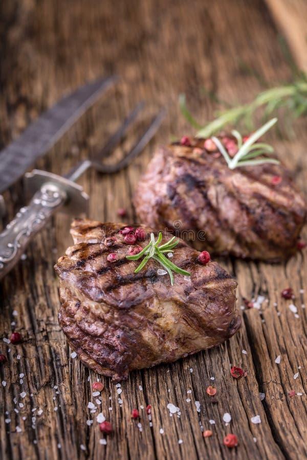Geroosterd rundvleeslapje vlees met rozemarijn, zout en peper op oude scherpe raad rundvlees royalty-vrije stock afbeelding