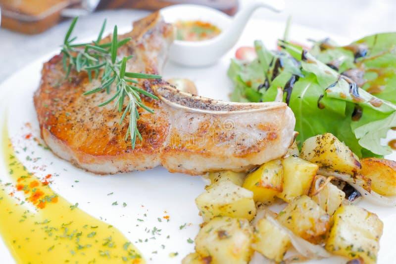 Geroosterd Varkenskoteletlapje vlees met aardappels en Organische salade royalty-vrije stock foto