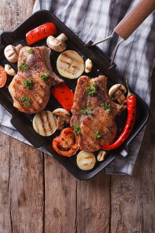 Geroosterd varkensvlees met paddestoelen in een pangrill Verticale hoogste mening stock foto