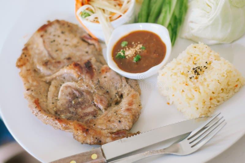 Geroosterd varkensvlees, papajasalade, groenten en rijst met kruidige saus stock fotografie