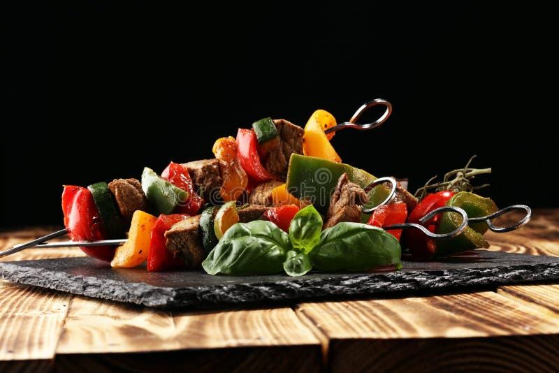 Geroosterd varkensvlees shish of kebab op vleespennen met groenten Voedselachtergrond shashlik royalty-vrije stock afbeeldingen