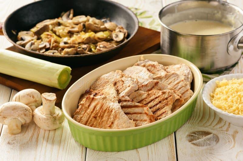 Geroosterd varkensvleeshaasbiefstuk met bechamelsaus, paddestoelen en fijngestampte aardappels Het koken procédé stock foto