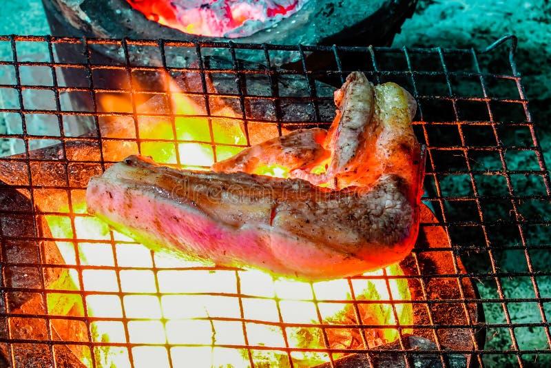 Geroosterd varkensvleeslapje vlees op de grillrooster, vlammen op achtergrond Barbecue en grill, heerlijk voedsel stock fotografie