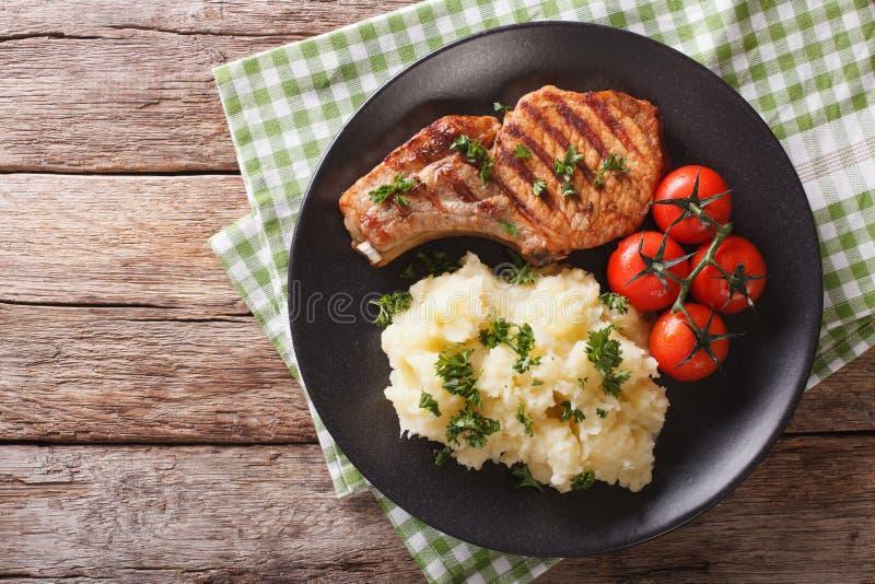 Geroosterd varkensvleeslendestuk met fijngestampte aardappels en tomatenclose-up Hori royalty-vrije stock afbeeldingen