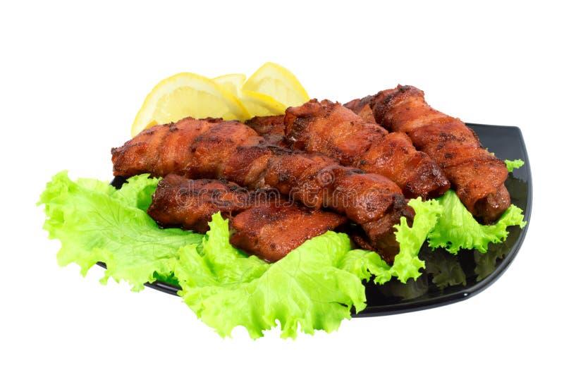 Geroosterd vlees, dat in bacon op de schotel wordt verpakt stock afbeelding