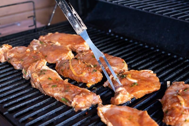 Geroosterd vlees, de tijd van de barbecuezomer Voorbereiding van vleesplakken in saus op brand Geroosterde BBQ Burgers Pasteitjes stock fotografie