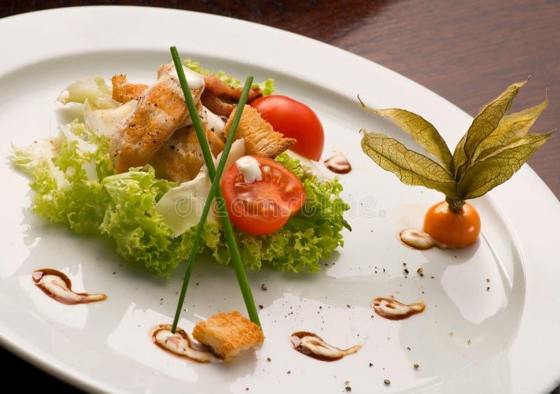 geroosterd vlees met salade en kersentomaten in een witte plaat stock afbeelding