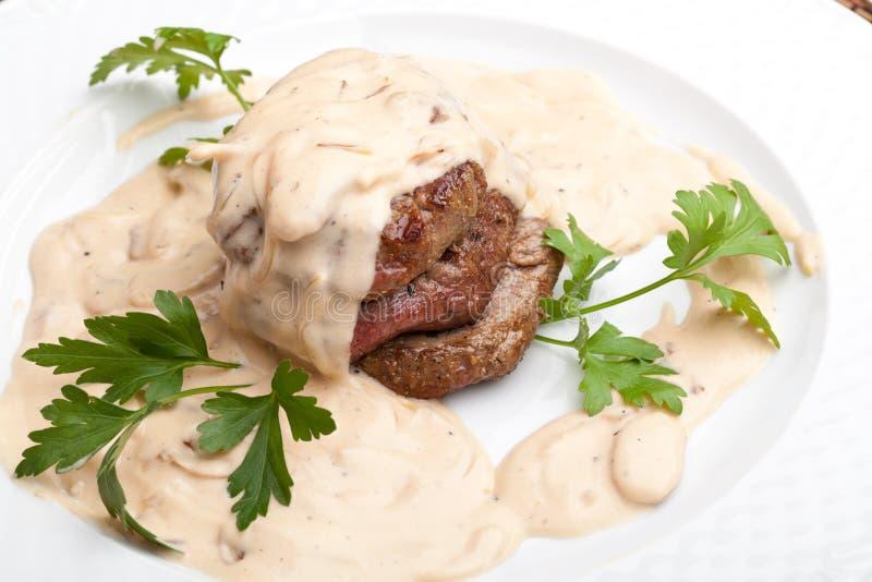 Geroosterd vlees onder witte saus stock fotografie