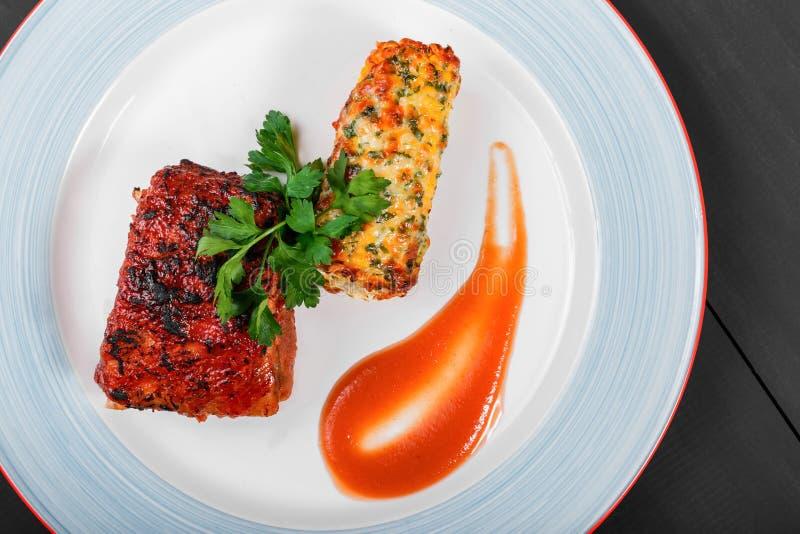 Geroosterd vleeslapje vlees met geroosterd graan in kaas en greens in plaat op donkere houten achtergrond Hete vleesschotels royalty-vrije stock afbeelding