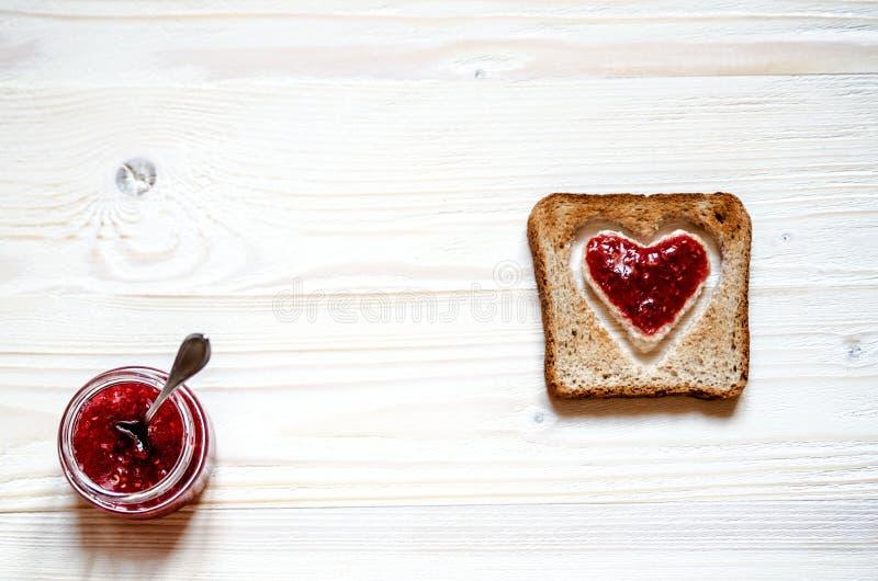 Geroosterd wit brood met een binnen hart Bij het hart met frambozenjam die wordt gepleisterd stock fotografie