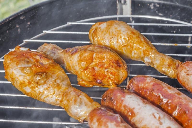 Geroosterd worsten en van kippenbenen close-up op de grill stock afbeelding