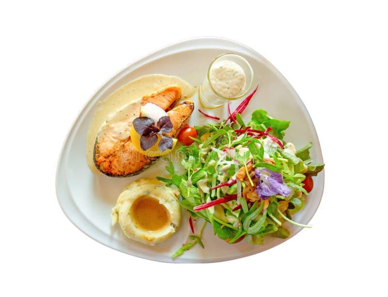 Geroosterd zalmlapje vlees dat op witte plaat met gemengde plantaardige salade, fijngestampte aardappels wordt gesneden, die in e royalty-vrije stock foto's