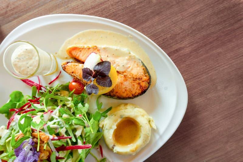 Geroosterd zalmlapje vlees dat op witte plaat met gemengde plantaardige salade wordt gesneden, fijngestampt aardappels en bovenst stock afbeelding