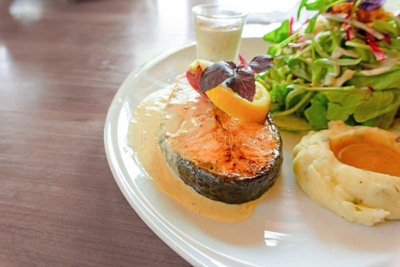 Geroosterd zalmlapje vlees dat op witte plaat met gemengde plantaardige salade wordt gesneden, fijngestampt aardappels en bovenst stock afbeeldingen