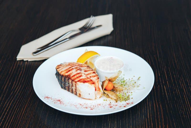 Geroosterd zalmlapje vlees met saus en citroen op een witte plaat houten lijst als achtergrond royalty-vrije stock foto