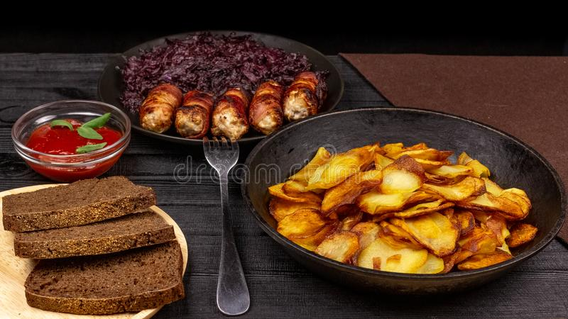 Geroosterde aardappel in de pot, stukken van rogge zwart brood op een houten dienende plaat, eigengemaakte worsten in bacon en ge royalty-vrije stock afbeeldingen
