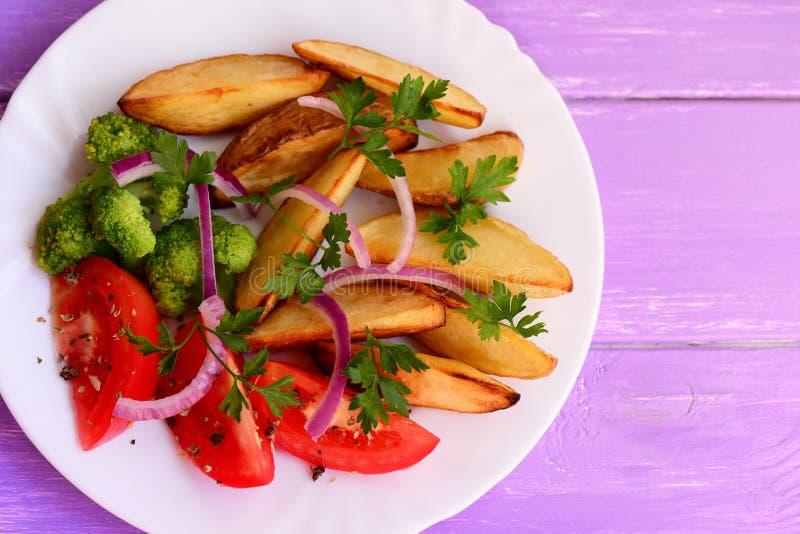 Geroosterde aardappelplakken, gekookte broccoli, verse tomaten met kruiden, rode ui, peterseliebladeren op een witte plaat stock afbeeldingen