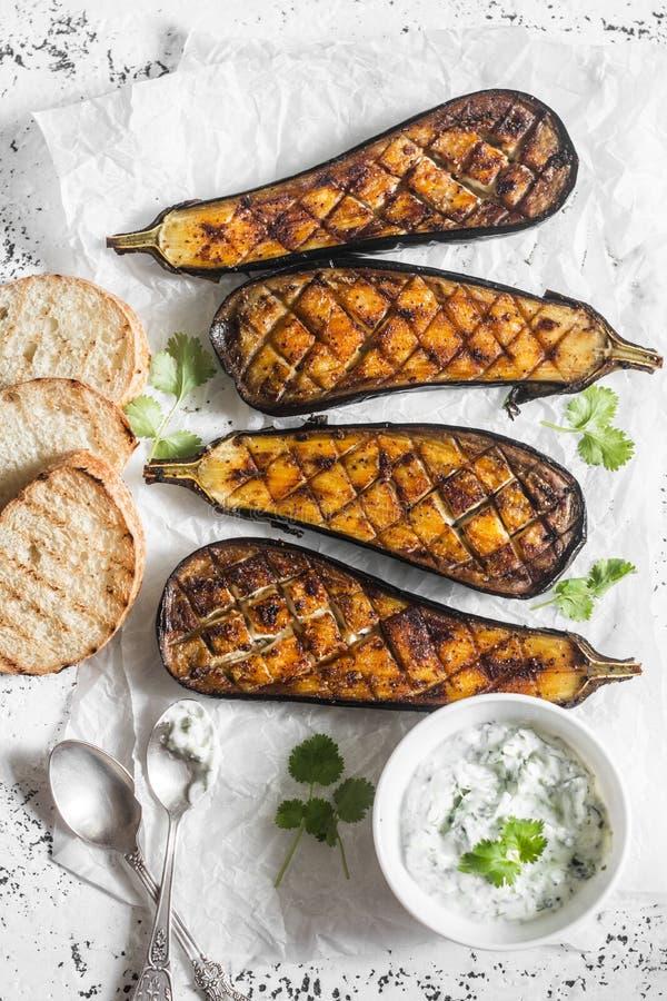 Geroosterde aubergine en saustzatziki op een lichte achtergrond, hoogste mening stock foto's
