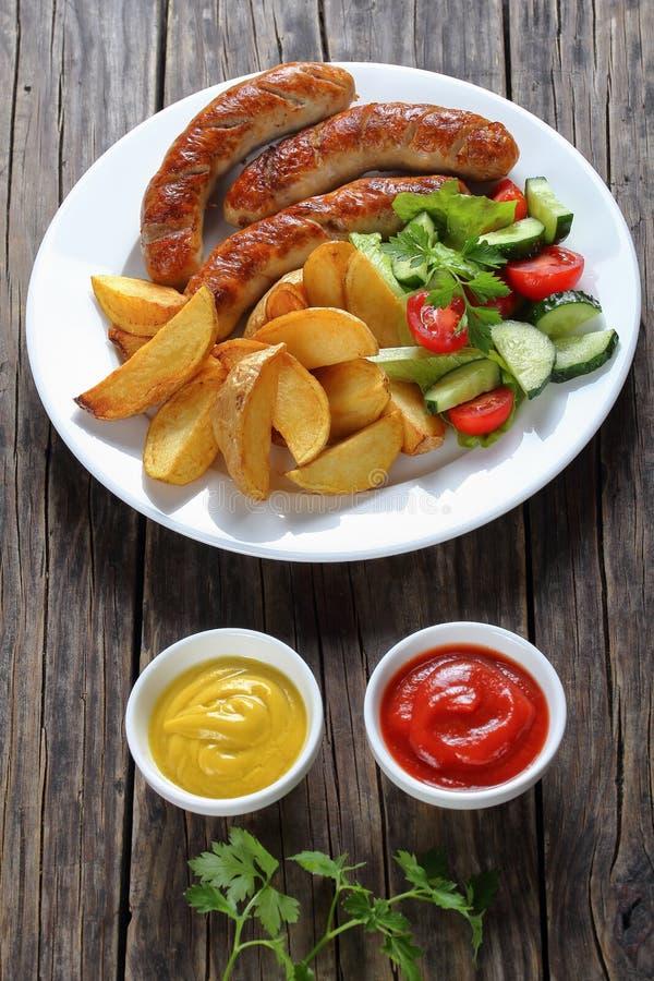 Geroosterde braadworst, salade, aardappels op plaat royalty-vrije stock afbeeldingen
