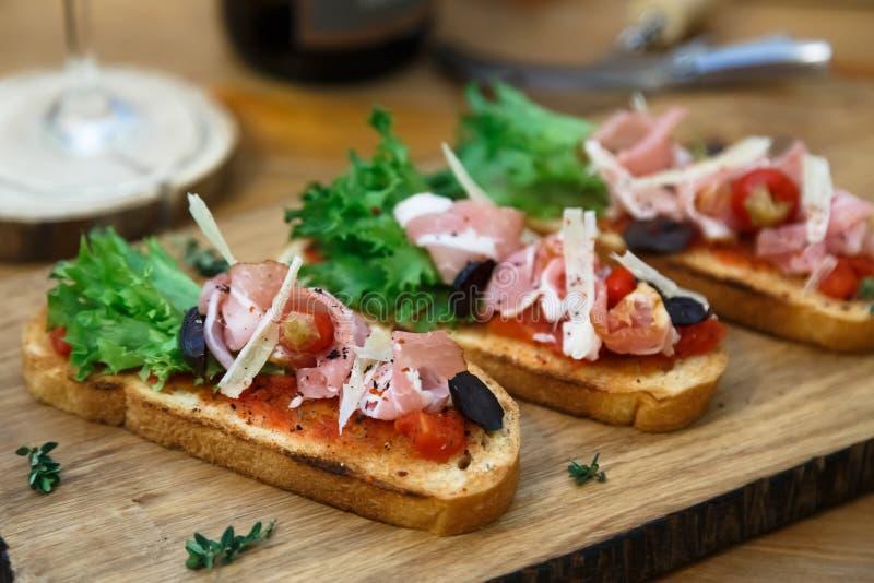 Geroosterde broodplak met gerookte ham en kaas stock afbeeldingen