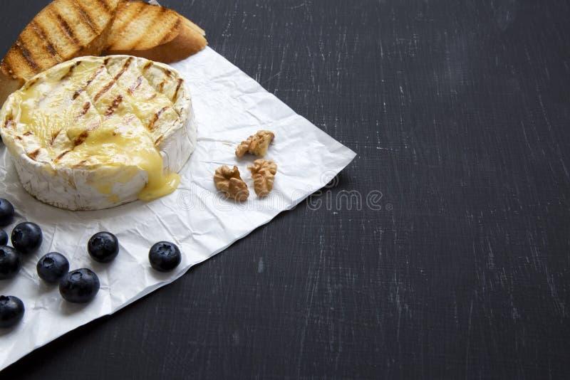 Geroosterde camembertkaas in document met toosts, bosbessen en okkernoten op donkere achtergrond, close-up Voedsel voor wijn De r royalty-vrije stock afbeelding