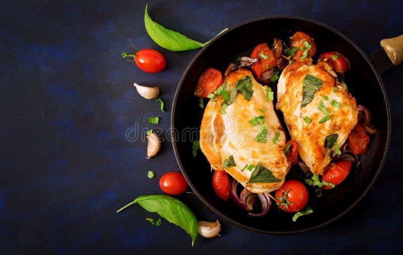 Geroosterde die Kippenborst met tomaten, knoflook en basilicum in pan wordt gevuld royalty-vrije stock foto's